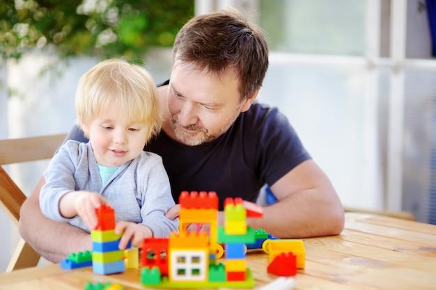 Petit garçon avec son père jouant avec des blocs en plastique colorés à la maison Photo Premium