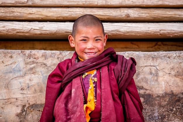Le petit garçon souriant des moines novices bouddhistes prie au monastère de boudhanath Photo Premium