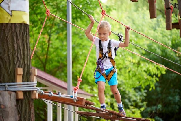 Petit garçon surmonte un obstacle dans un parc d'attractions Photo Premium
