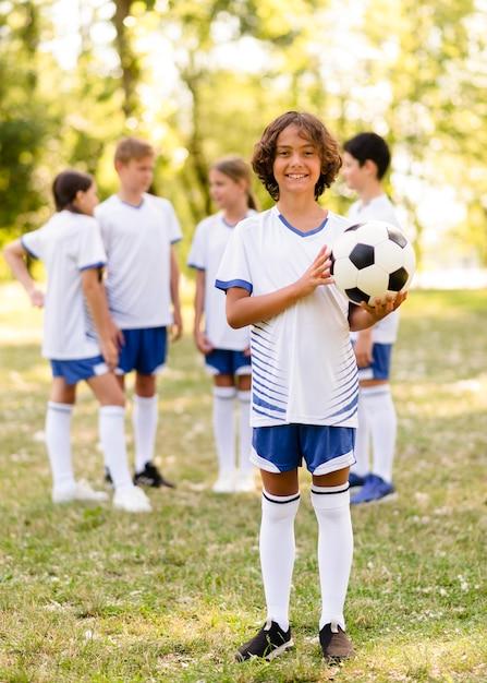 Petit Garçon Tenant Un Ballon De Football à L'extérieur à Côté D'autres Enfants Photo gratuit