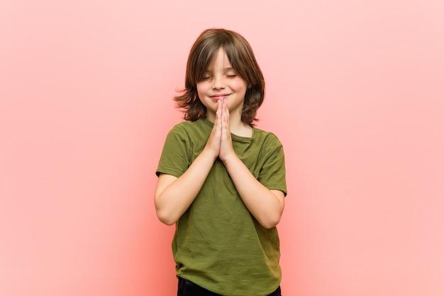 Petit garçon tenant par la main pour prier près de la bouche, se sent confiant. Photo Premium