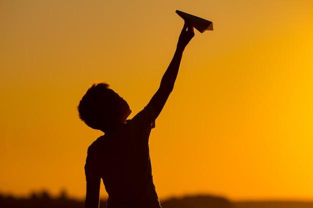 Petit garçon tient un avion en papier dans sa main au coucher du soleil. un enfant lève la main au ciel et joue avec l'origami le soir dans la rue Photo Premium