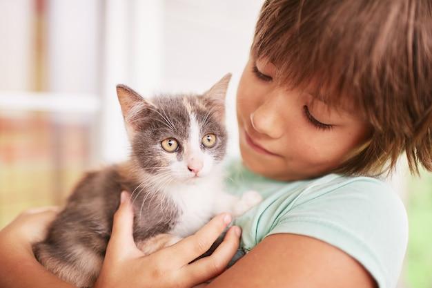 Petit garçon tient un chat noir et blanc sur son épaule Photo gratuit
