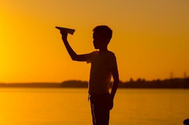 Un petit garçon tient son origami au coucher du soleil le soir. il joue avec un avion qui s'est fait près de la rivière Photo Premium