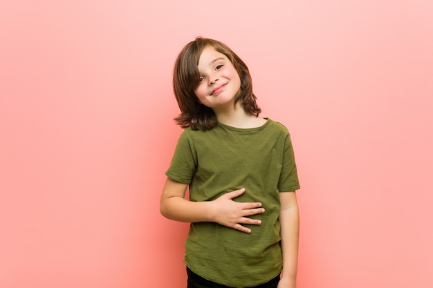 Petit garçon touche le ventre, sourit doucement, concept de manger et de satisfaction. Photo Premium