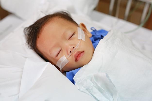 Petit garçon avec un tube respiratoire dans le nez recevant un traitement médical. soins intensifs à l'hôpital. Photo Premium