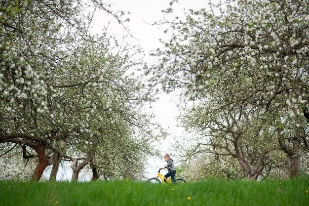 Petit garçon à vélo jaune dans le jardin de printemps. enfant, cyclisme, belle nature et concept de style de vie Photo Premium