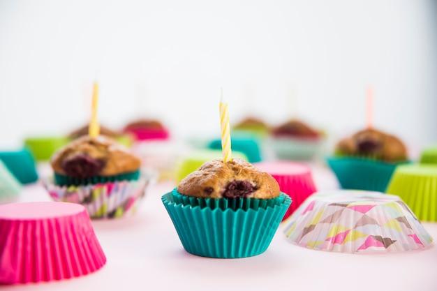 Petit gâteau d'anniversaire dans les porte-papiers avec des bougies Photo gratuit