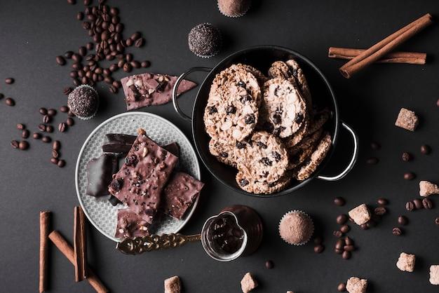 Petit gâteau; biscuits et truffes au chocolat à base de grains de café et de chocolat sur fond noir Photo gratuit
