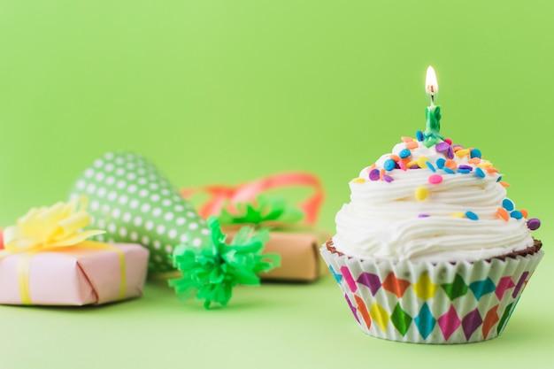 Petit gâteau frais avec une bougie illuminée sur une surface verte Photo gratuit