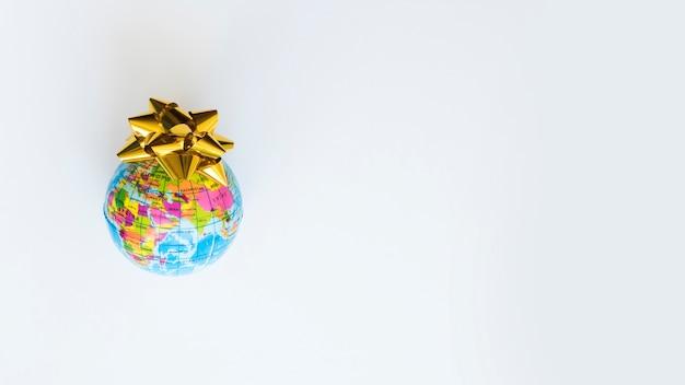 Petit globe avec un arc jaune sur la table Photo gratuit