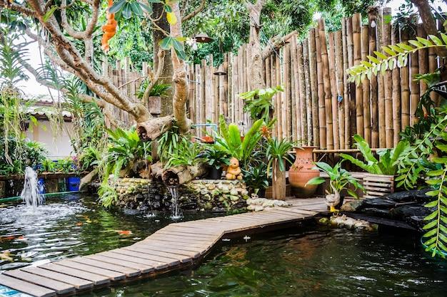 Petit jardin avec bassin de poissons koi et mur de bambou décoré Photo Premium