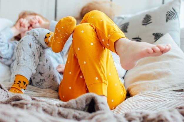 Petit joli frère et soeur en pyjama couché dans un lit, confortable m Photo Premium
