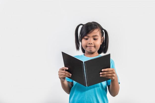 Petit livre de lecture fille en studio tourné Photo gratuit