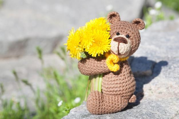 Un petit ours brun tricoté avec une écharpe jaune dans un jardin d'été. jouet tricoté à la main, amigurumi Photo Premium