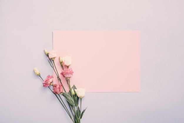 Petit papier avec des fleurs roses sur une table lumineuse Photo gratuit