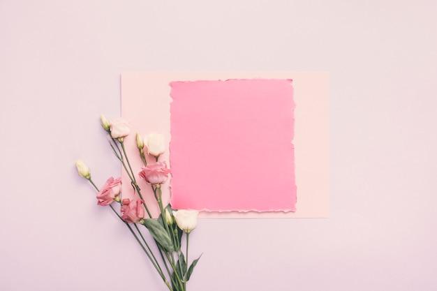 Petit papier avec des fleurs roses sur la table Photo gratuit