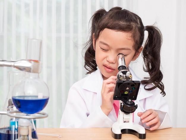 Petit rôle de jolie fille asiatique jouant un scientifique dans un laboratoire scientifique et apprenant à utiliser un microscope. Photo Premium