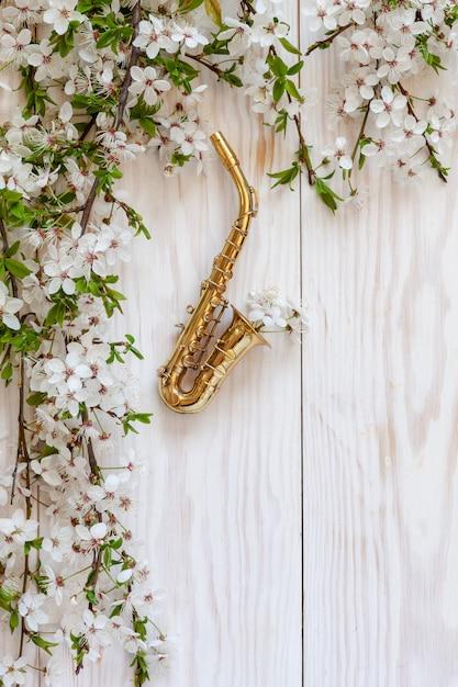 Petit saxophone doré et branches de cerisier en fleurs. Photo Premium