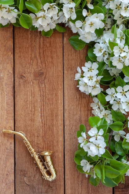 Petit saxophone doré et branches de pommier florissant. Photo Premium