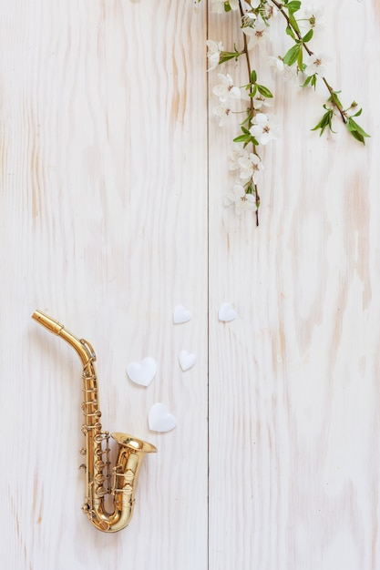 Petit saxophone doré, figurines en forme de cœur blanc et branches de cerisier en fleurs. Photo Premium