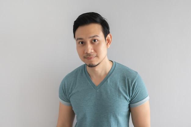 Petit sourire visage d'homme pas sûr en t-shirt bleu sur fond gris. Photo Premium