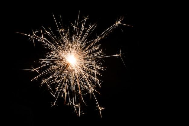 Un petit sparkler de nouvel an sur fond noir. Photo Premium