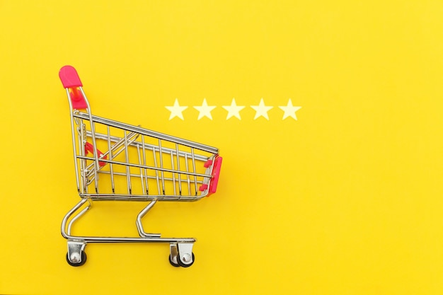 Petit Supermarché épicerie Pousser Panier Pour Faire Du Shopping Jouet Avec Roues Et 5 étoiles Classement Isolé Sur Fond Jaune. Consommateur De Détail Achetant Un Concept D'évaluation Et D'examen En Ligne. Photo Premium
