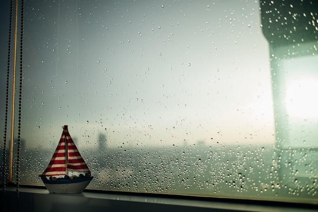 Petit voilier au bord des fenêtres pluvieuses. Photo Premium