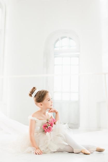 La Petite Balerina En Tutu Blanc En Classe à L'école De Ballet Photo gratuit