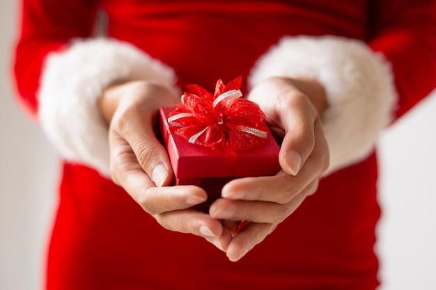 Petite boîte cadeau rouge avec un arc dans les mains féminines Photo gratuit