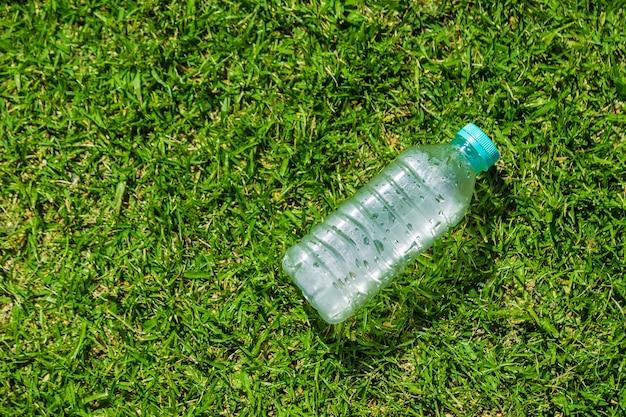 Petite bouteille d'eau froide couchée sur un terrain herbeux vert par une journée chaude et ensoleillée avec une chambre Photo Premium