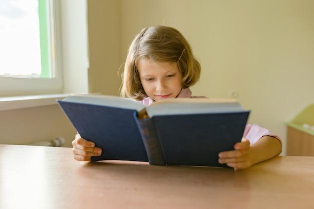 Petite étudiante est assise à un bureau avec un livre Photo Premium