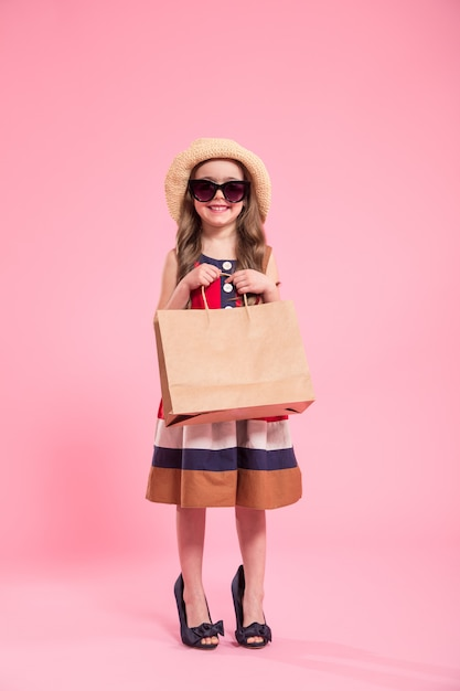 Petite Fashionista Sur Fond Coloré Dans Les Chaussures De Maman Photo gratuit