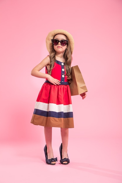 Petite Fashionista Avec Un Sac à Provisions Dans Un Chapeau D'été Et Des Lunettes, Sur Un Fond Rose De Couleur Dans Les Chaussures De Maman, Le Concept De La Mode Pour Enfants Photo gratuit