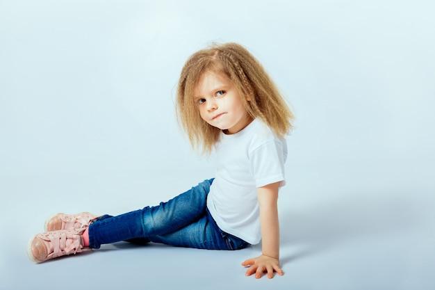 Petite Fille De 4 Ans Aux Cheveux Bouclés Portant Une Chemise Blanche, Un Jean Bleu, Des Bottes Roses Assis Sur Le Sol, Souriant Et Regardant La Caméra. Photo Premium