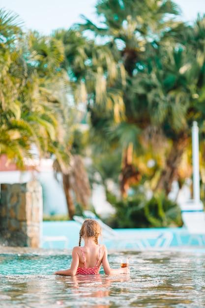 Petite fille adorable dans la piscine extérieure Photo Premium