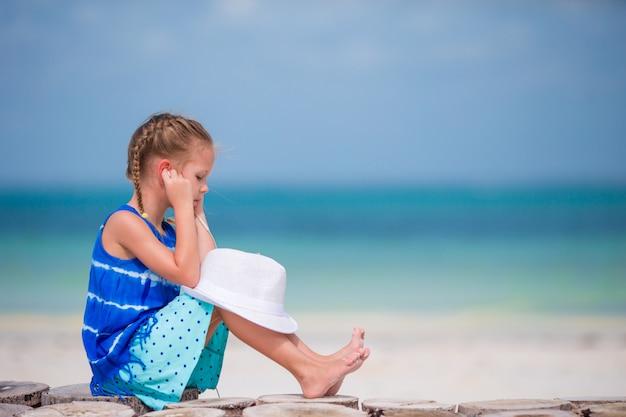 Petite fille adorable, écoutant de la musique sur un casque sur la plage Photo Premium