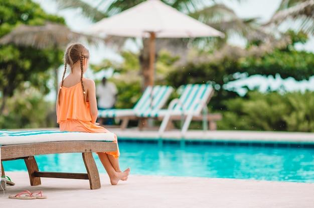 Petite fille adorable heureuse dans la piscine extérieure Photo Premium