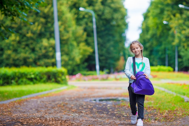 Petite fille adorable va à la gym avec son sac de sport Photo Premium