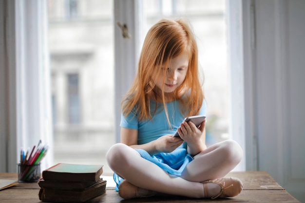 Petite fille à l'aide d'un smartphone Photo Premium