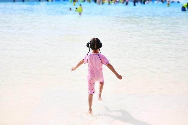 Petite fille aime et courir dans la grande piscine extérieure en vacances. Photo Premium