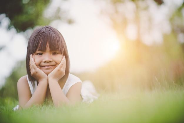 Petite fille allongée confortablement sur l'herbe et souriant Photo gratuit