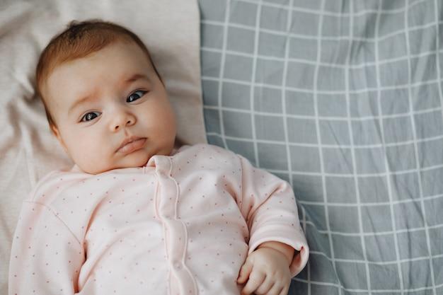 Petite Fille Allongée Sur Le Dos Sur Le Lit Dans Une Chambre Lumineuse, Vêtue D'une Robe D'été Légère. Bébé Calme Bébé De 3 Mois. Copie Espace Photo Premium