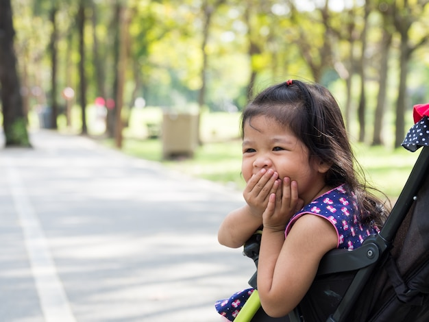 Petite fille asiatique assis dans une poussette au parc public Photo Premium