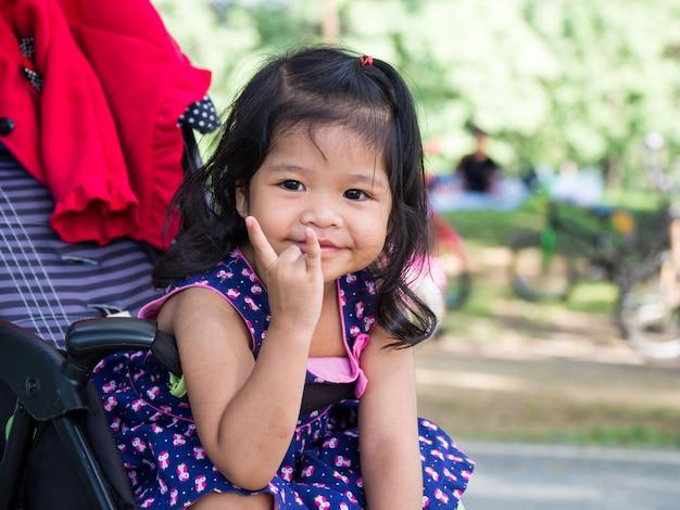 Petite fille asiatique assise dans une poussette au parc public. Photo Premium