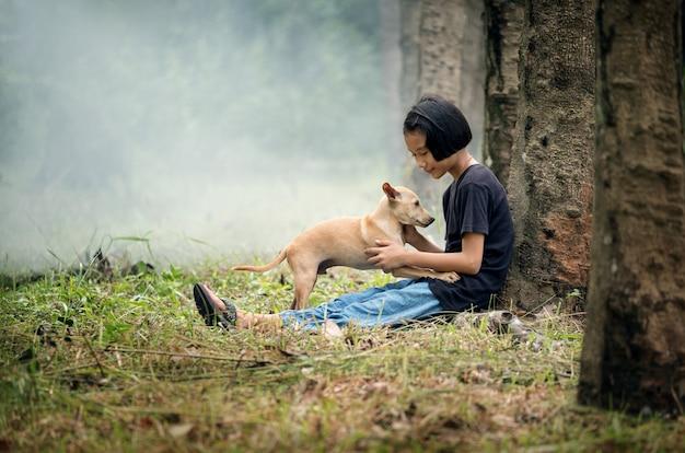 Petite fille asiatique assise seule sur un champ vert sous l'arbre avec son chien, en plein air à la campagne de la thaïlande Photo Premium