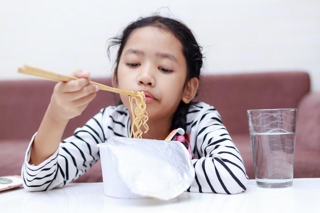 Petite fille asiatique assise à une table blanche pour manger des nouilles instantanées Photo Premium
