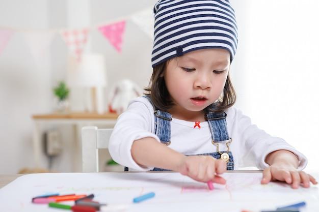 Petite Fille Asiatique Assise à Table Dans La Chambre, Fille D'âge Préscolaire, Dessin Sur Papier Avec Des Stylos Colorés Par Journée Ensoleillée, Jardin D'enfants Ou Photo Premium