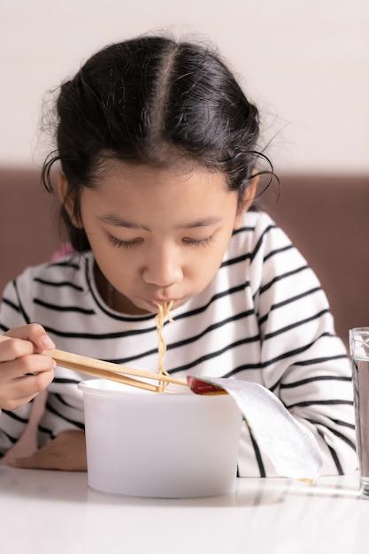 Petite Fille Asiatique Assise à Un Tableau Blanc Pour Manger Des Nouilles Instantanées Sélectionner Le Focus Faible Profondeur De Dossier Photo Premium